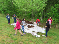 Girl Scouts show how preparing beds for pollinator-friendly plants is done.